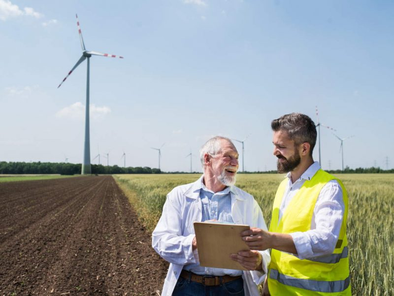 Two engineers or technicians with clipboard standing on wind farm, making notes.