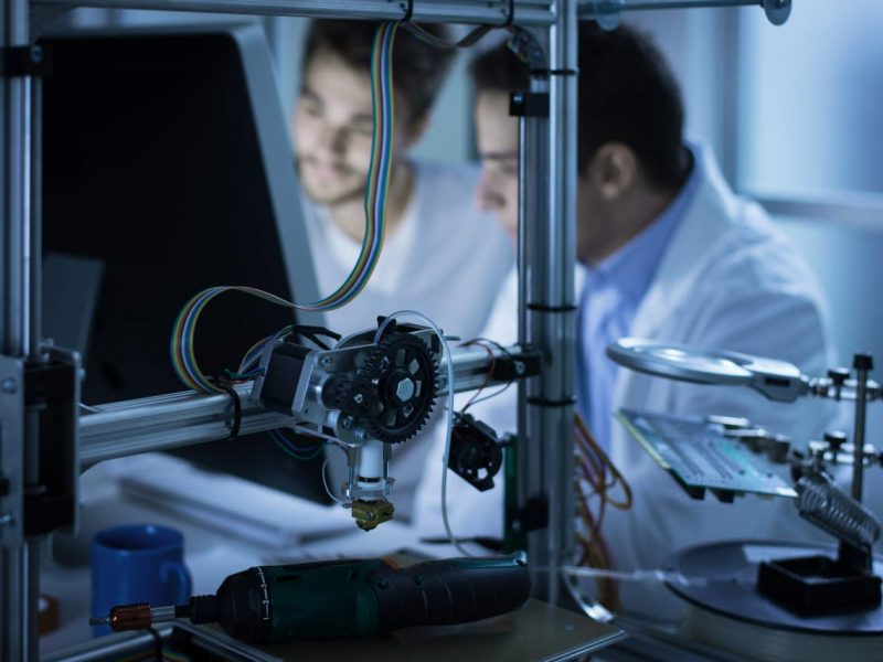 Young engineers working in the laboratory and using a computer, 3D printer on foreground, science and technology concept